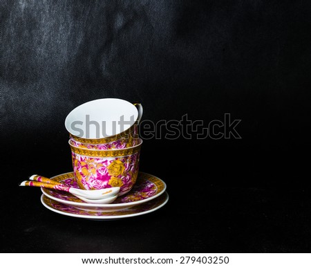 two vintage cups, sauceres and spoons on a black background - stock photo