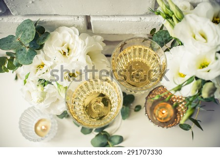Two vintage glasses of champagne and white flowers, candles on white table by the brick wall background. Festive summer home party decor, top view. - stock photo