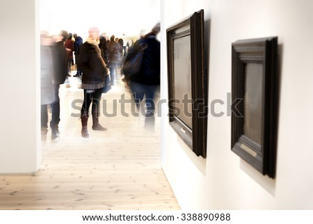Two vintage picture frames on wall in art museum, with crowd of visitors in blurred motion in background