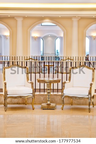 Two vintage style armchairs upholstered in cream fabric with a table between them standing against a railing with a backdrop of arches in a luxury interior - stock photo