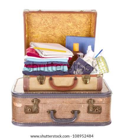 two vintage suitcases packed and open showing contents isolated on white - stock photo