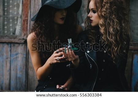 Two vintage witches perform magic ritual, with elixir in hand on the eve of Halloween