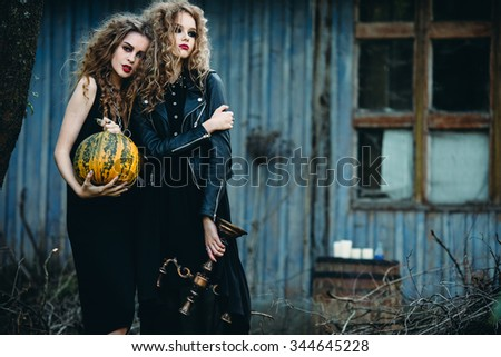 two vintage women as witches, posing in front of an abandoned house on the eve of Halloween - stock photo