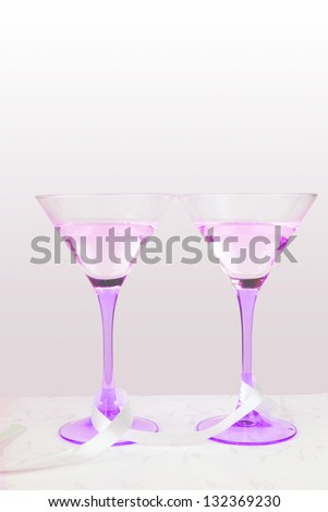 two violet glasses with ribbon on a tablecloth