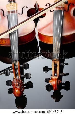 Two violins on dark background - stock photo