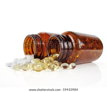 Two vitamin bottles, side-by-side with spilled contents on white