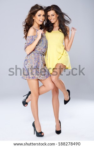 Two vivacious beautiful young women in trendy short summer dresses posing arm in arm balanced on one foot smiling at the camera, full length studio portrait - stock photo