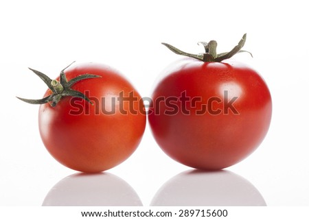 Two vivid red glossy fresh tomatoes isolated white reflected at the studio. - stock photo