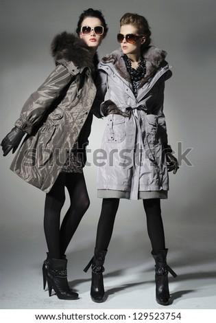 Two Vogue style in coat dresses. Studio portrait - stock photo