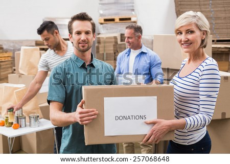 Two volunteers holding a donations box in a large warehouse - stock photo