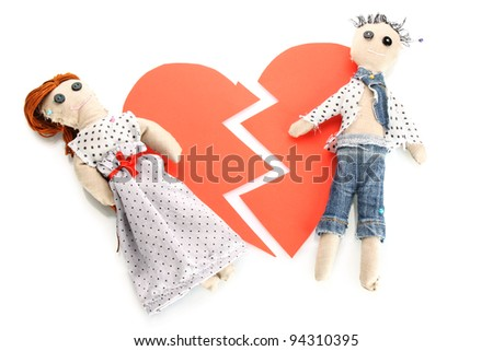Two voodoo dolls boy and girl on the broken heart isolated on white - stock photo