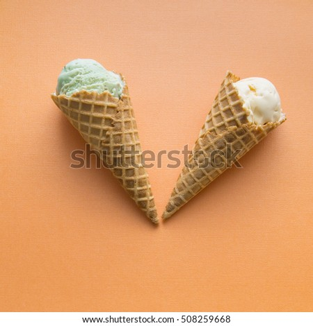 Two waffle cones with small portions of pistachio and vanilla gelato ice cream. selective focus.