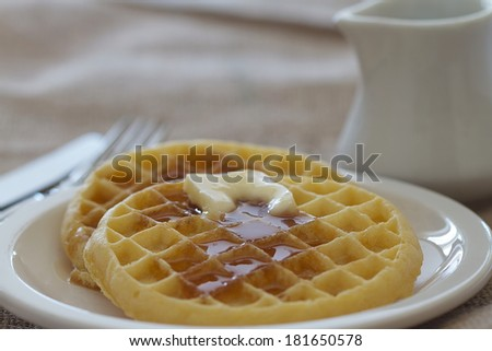 Two waffles with butter and syrup - stock photo