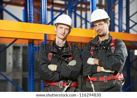 Two warehouse installation staff male workers in uniform in front of pallet rack arrangement stillages - stock photo