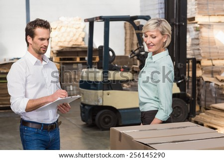 Two warehouse managers checking inventory in a large warehouse - stock photo