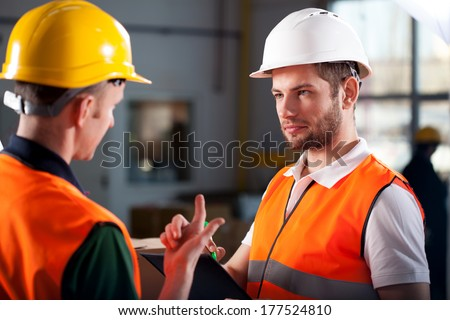 Two warehouse workers discussing about new project - stock photo
