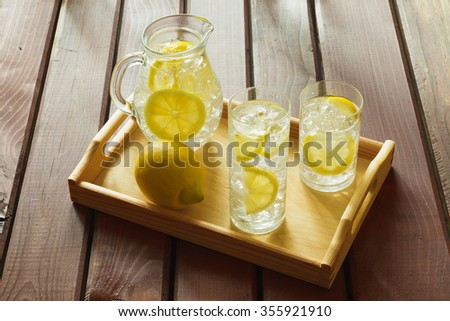 Two water drinks with lemon on wooden tray with ice and condensation on glass - stock photo