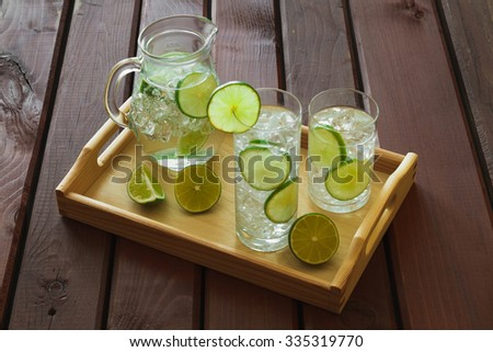 Two water drinks with lime on wooden tray with ice and condensation on glass - stock photo