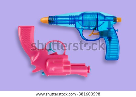 Two water pistols isolated on violet background - stock photo