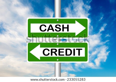 Two way street road sign pointing to Cash and Credit with a blue sky in a background