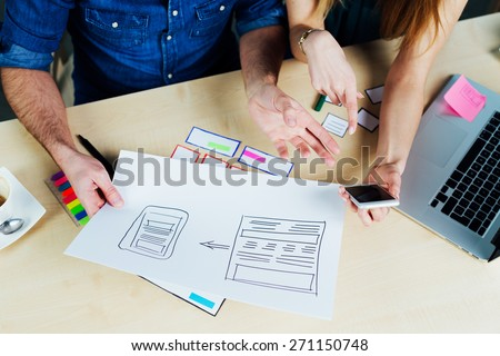 Two web designers brainstorming for ideas and sketching - stock photo