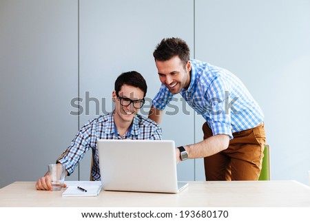 Two web designers looking at a website they designed - stock photo
