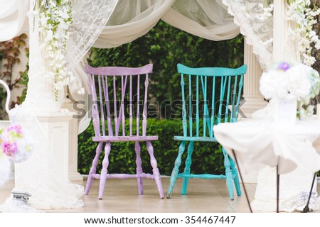 two wedding chairs in decorated arbor