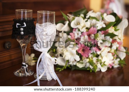 Two wedding glasses and bridal bouquet on stone in summer garden - stock photo