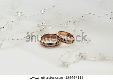 Two wedding rings from yellow and  gold lie on a veil of the bride - stock photo