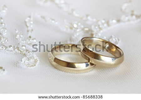 Two wedding rings from yellow gold lie on a dress of the bride - stock photo