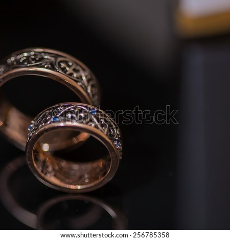 Two wedding rings in infinity sign on black background. Love concept. - stock photo