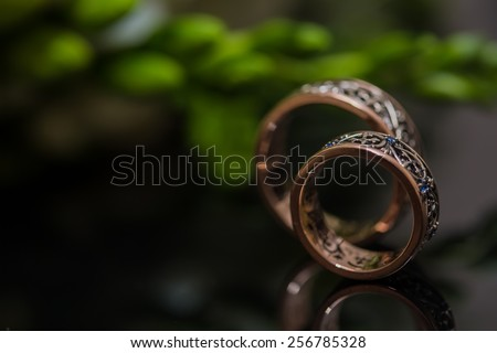 Two wedding rings in infinity sign with bouquet on black background. Love concept. - stock photo
