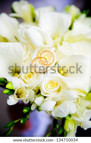 Two wedding rings lie on a bouquet of white roses.  Rings are golden.