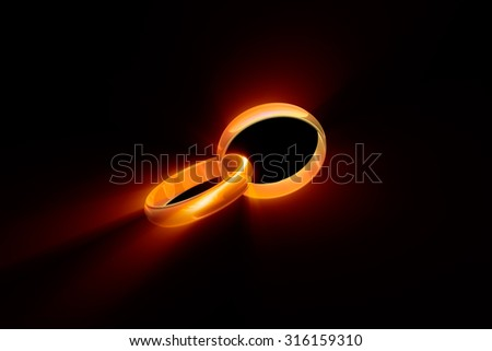 Two wedding rings on a black background. Used a glow effect.  - stock photo