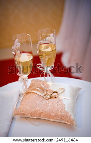 two wedding rings on a cushion on the background glasses of champagne. - stock photo