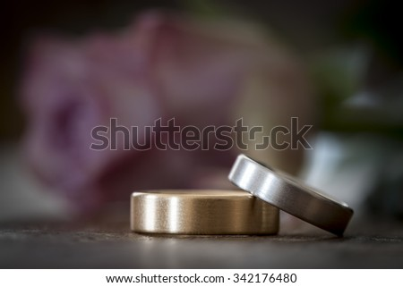 Two wedding rings on a wooden surface with rose - stock photo