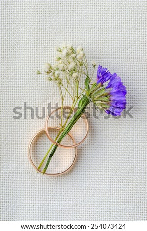 two wedding rings with a flower on a flax background - stock photo