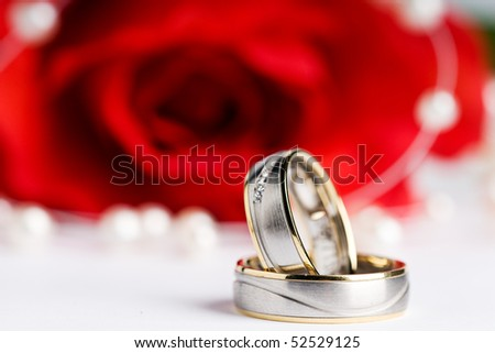 two wedding rings with a pearl necklace and a red rose in the background - stock photo