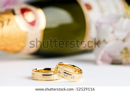 two wedding rings with flowers and a champagne bottle in the background - stock photo