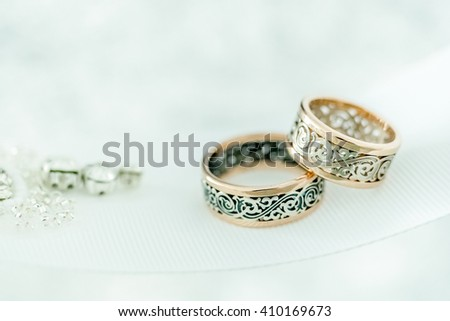 Two wedding rings with rare design on white broad ribbon