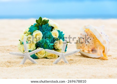 Two wedding rings with two starfish, wedding bouquet and a large shell on a sandy tropical beach. Wedding and honeymoon in the tropics. - stock photo