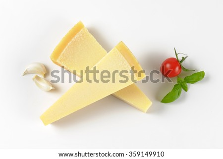 two wedges of fresh parmesan cheese and garnish on white background - stock photo