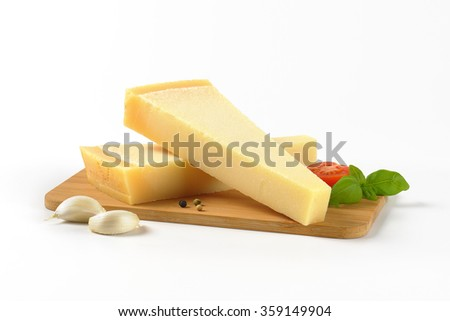 two wedges of fresh parmesan cheese and garnish on wooden cutting board - stock photo
