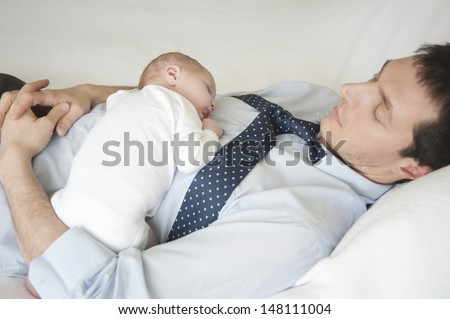 Two week newborn baby sleeping with father in bed - stock photo