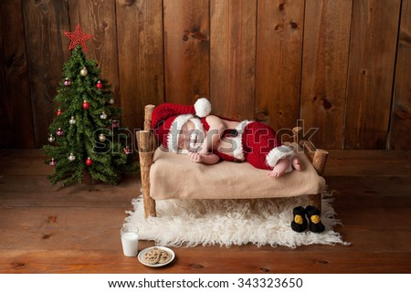 Two week old, newborn, baby boy wearing a crocheted Santa suit and sleeping on a tiny, wooden bed. Shot in the studio with props, including a Christmas tree, glass of milk and crocheted cookies.  - stock photo