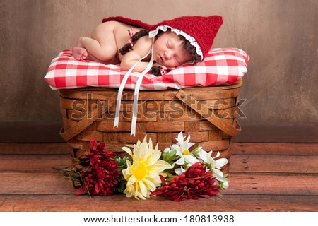 Two week old newborn baby girl dressed as Little Red Riding Hood and sleeping on a vintage wooden picnic basket surrounded with flowers. - stock photo