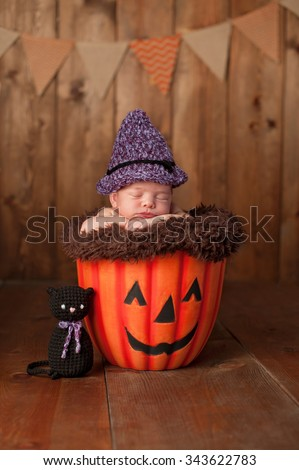 Two week old newborn baby girl wearing a witch costume. She is sleeping in a Jack-O-Lantern. Shot in the studio with a rustic wood background.