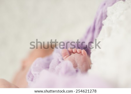 Two weeks newborn's feet under violet blanket - stock photo