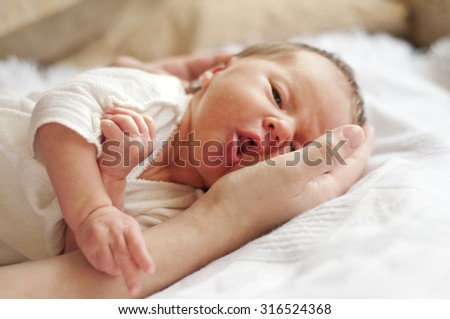 Two weeks old baby on the arm - stock photo
