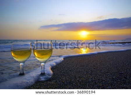 two weeping wineglasses on the sand in the wave foam and sunset - stock photo